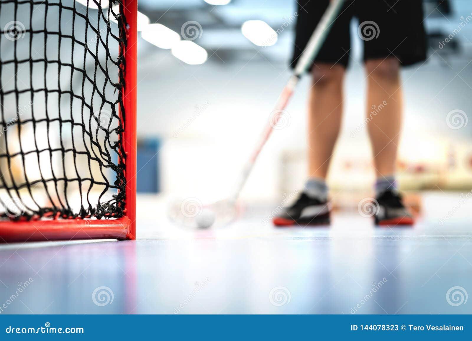 Floorball mål och netto Spelareutbildning i bakgrunden Man som spelar golvhockey