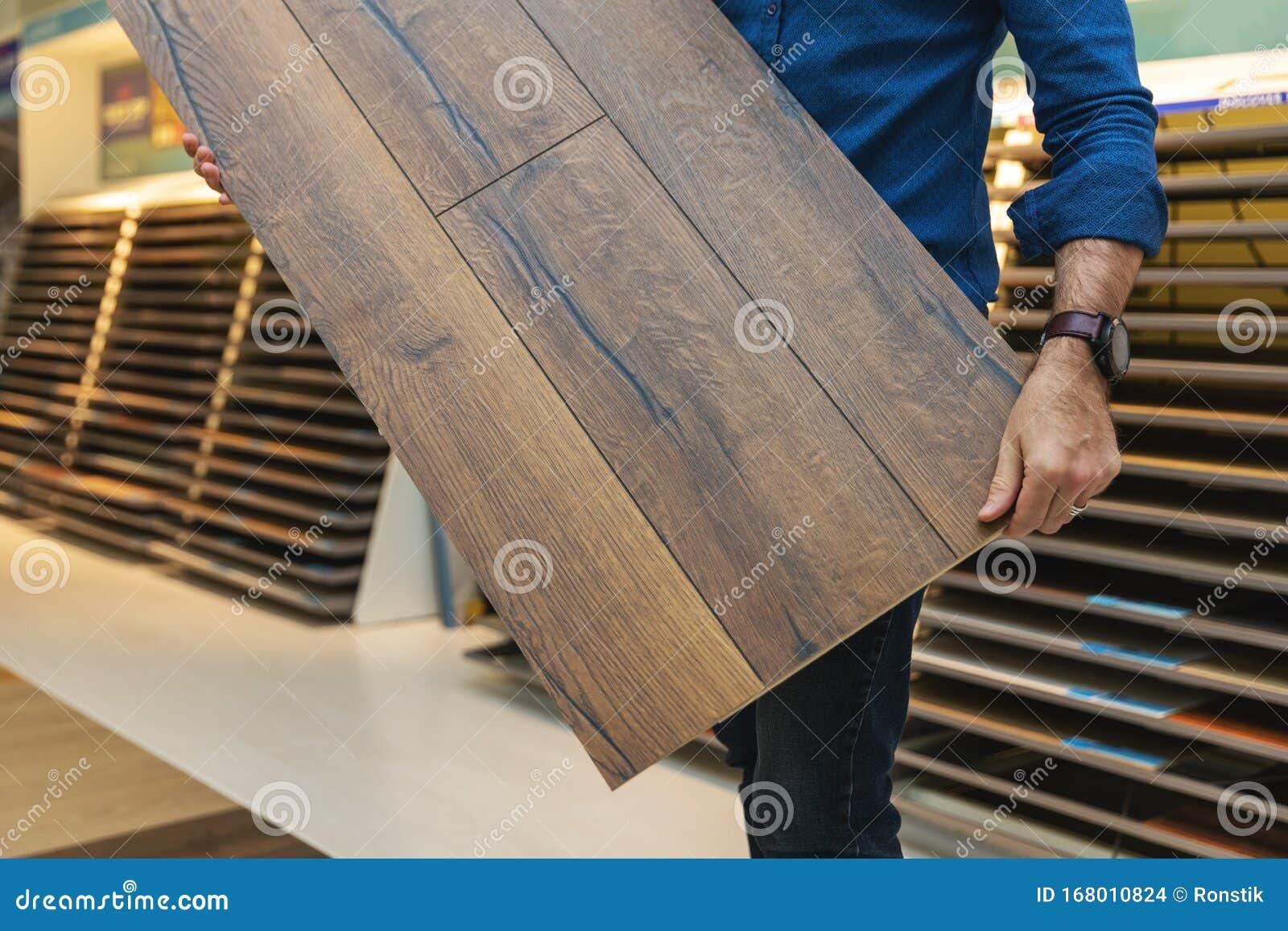 Flooring Store Salesman With Laminate Floor Sample Panel Stock