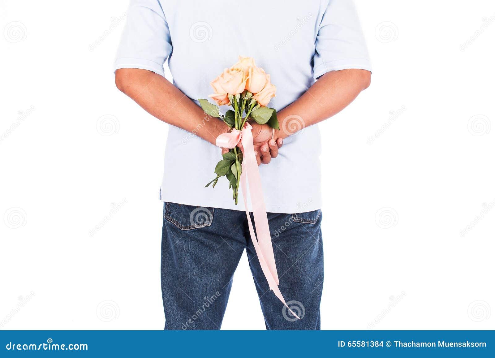 Flor cor-de-rosa da posse do homem atrás para a surpresa sua esposa