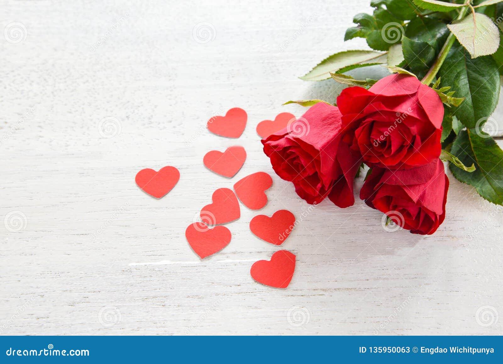 Flor cor-de-rosa vermelha do dia de Valentim no fundo de madeira branco/no coração vermelho pequeno amor romântico