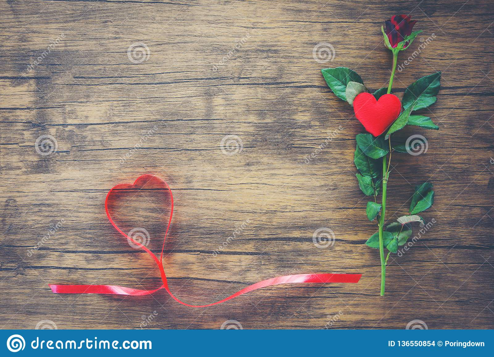 Flor cor-de-rosa vermelha do dia de Valentim no fundo de madeira/coração vermelho com rosas