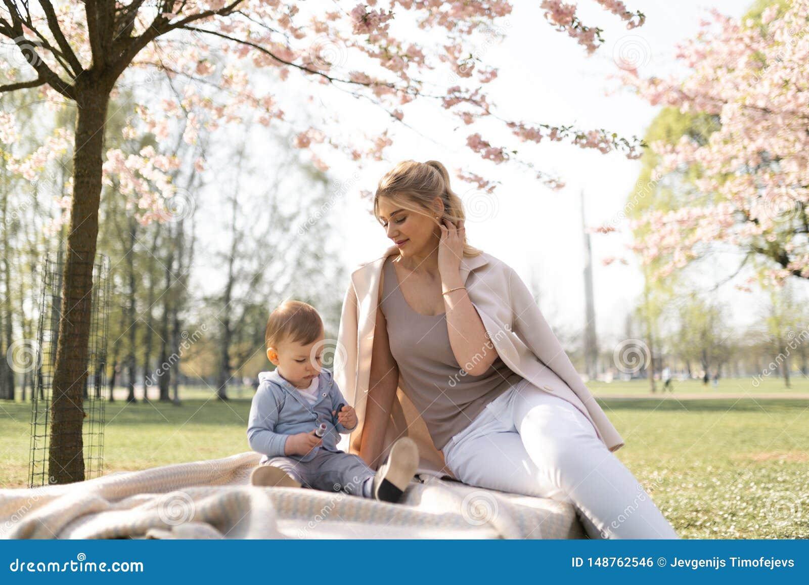 Flor de cerejeira de Sakura - m?e nova da mam? que senta-se com seu filho do beb? do rapaz pequeno em um parque em Riga, Let?nia