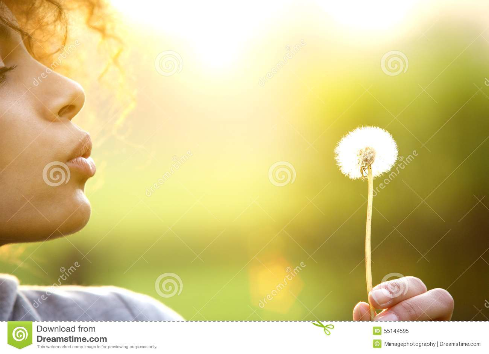 Flor de sopro do dente-de-leão da jovem mulher fora