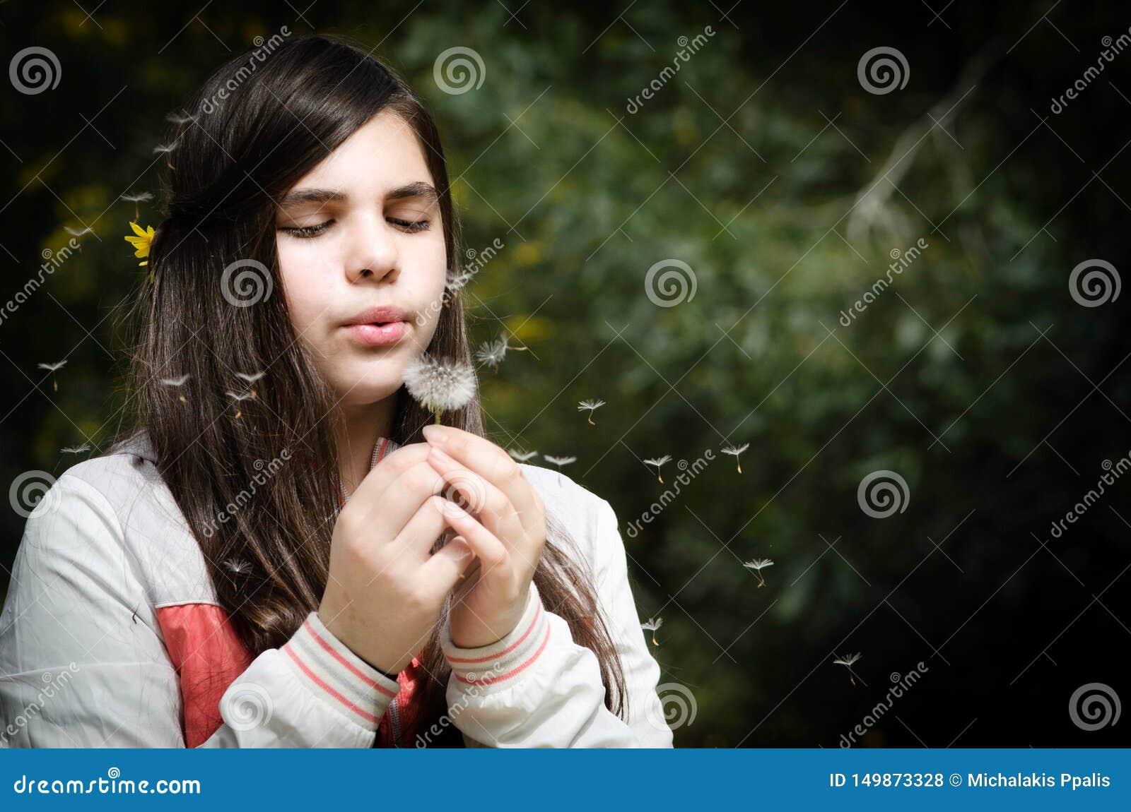 Flor de sopro do dente-de-leão da menina bonita nova