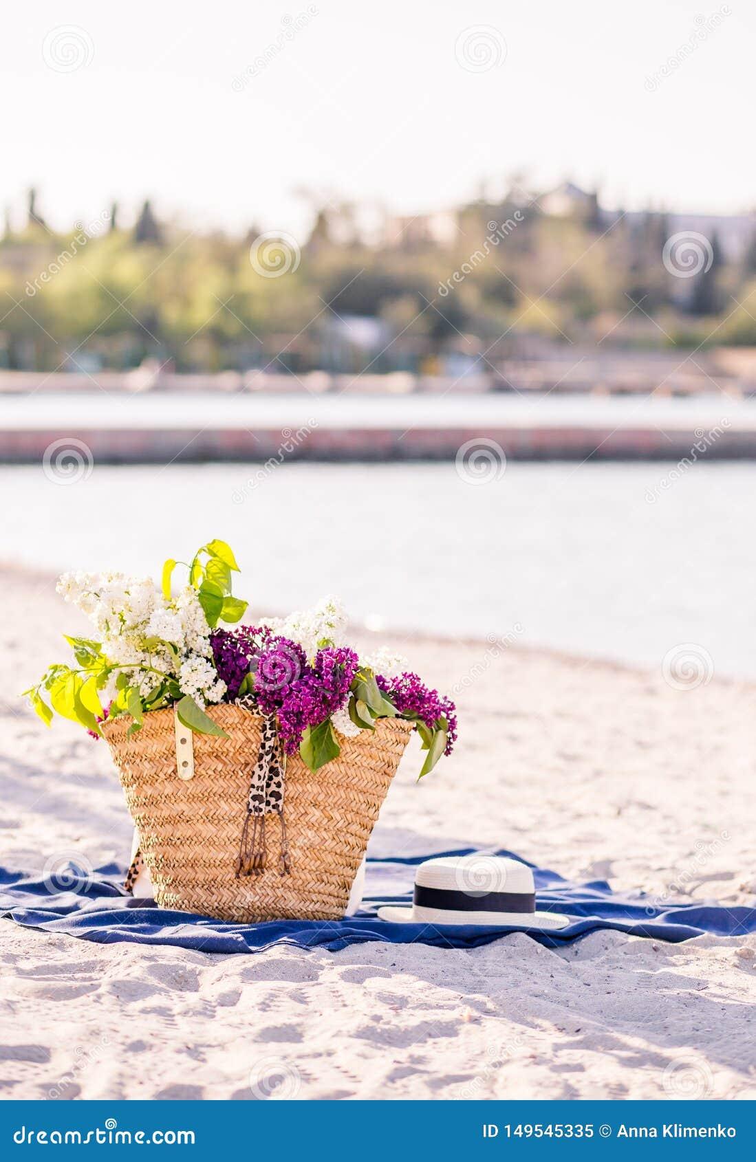 Flor do lil?s Chapéu do verão das mulheres com uma fita e um ramalhete de flores lilás em um fundo azul Vista superior Configura?