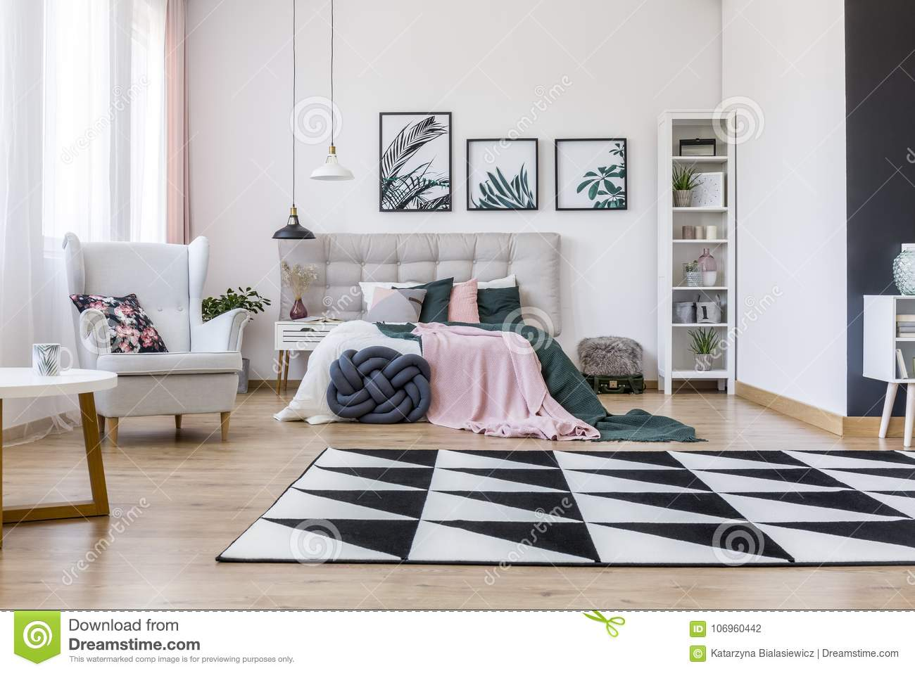 Floral Pillow On Beige Armchair Near Bed With Pink And Green Bedsheets In  Bedroom Interior With Geometric Carpet