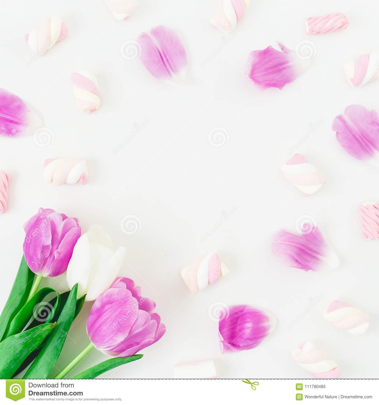 Floral round frame with pink tulips with petals and marshmallow on white background. Flat lay, Top view.