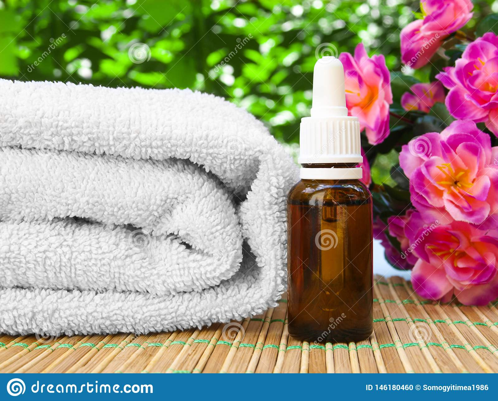 Floral spa and wellness design with oil bottle, towel