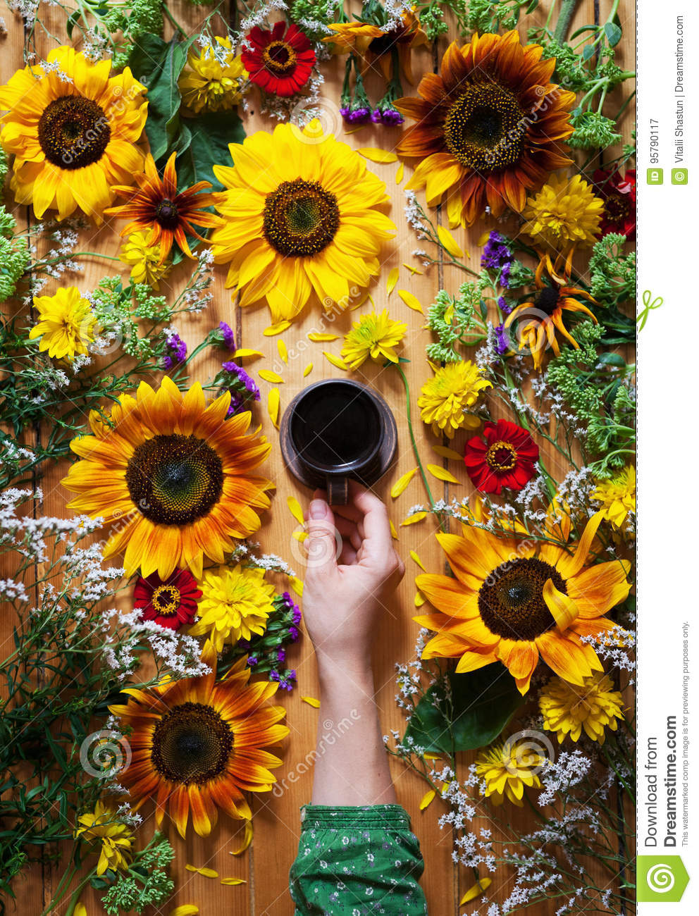 Floral summer background. A mug of coffee in a woman`s hand on a wooden background with sunflowers and wildflowers