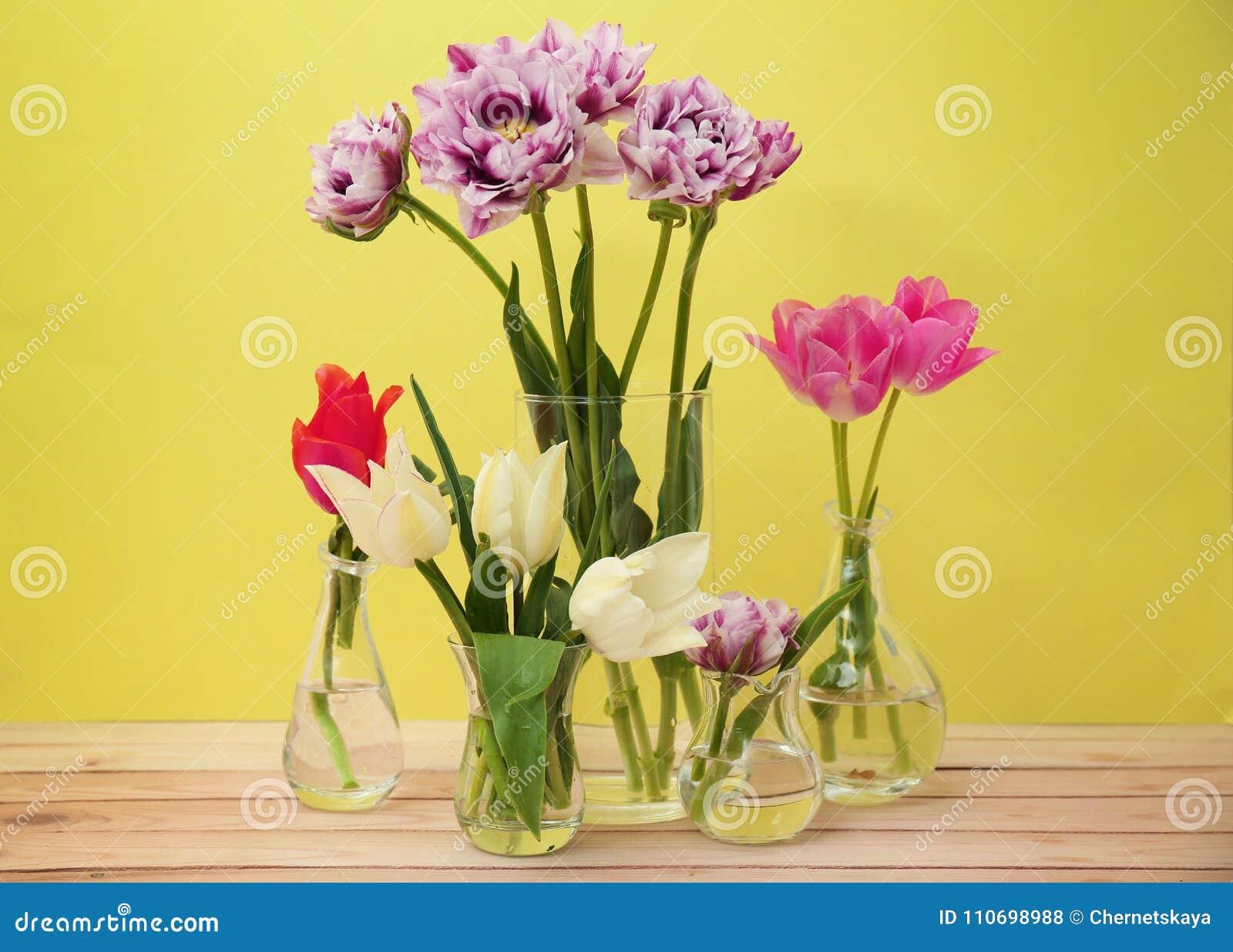 Floreros de cristal con los tulipanes hermosos