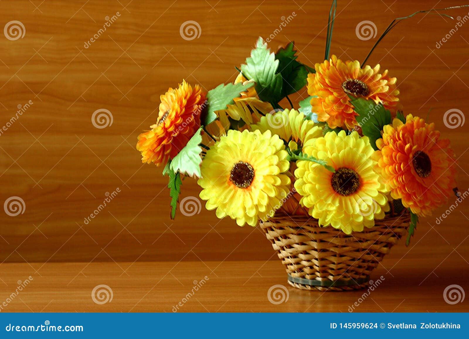 Flores artificiais decorativas brilhantes em uma cesta tecida para seu desktop