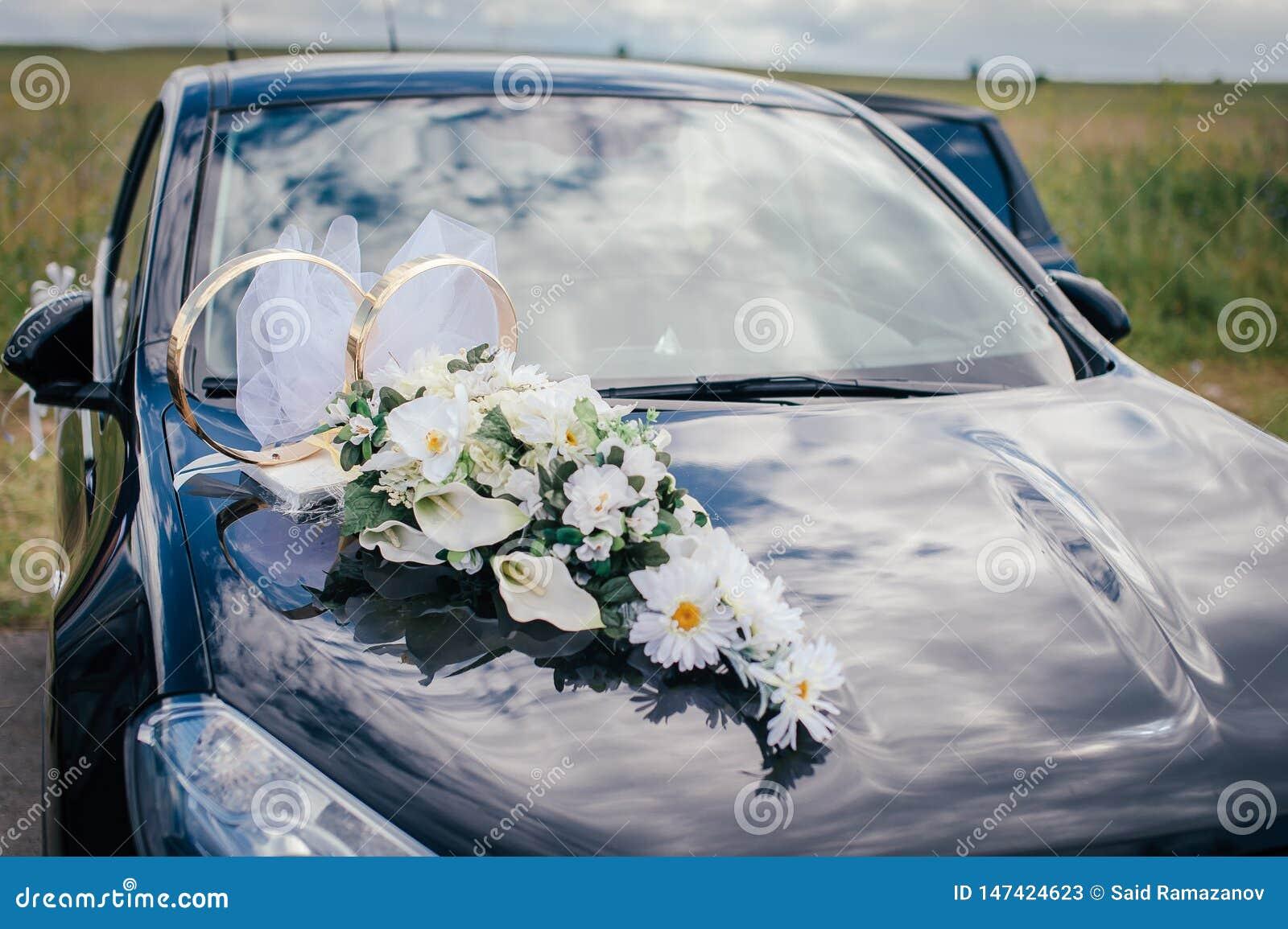 Flores brancas e alianças de casamento na capa do carro preto