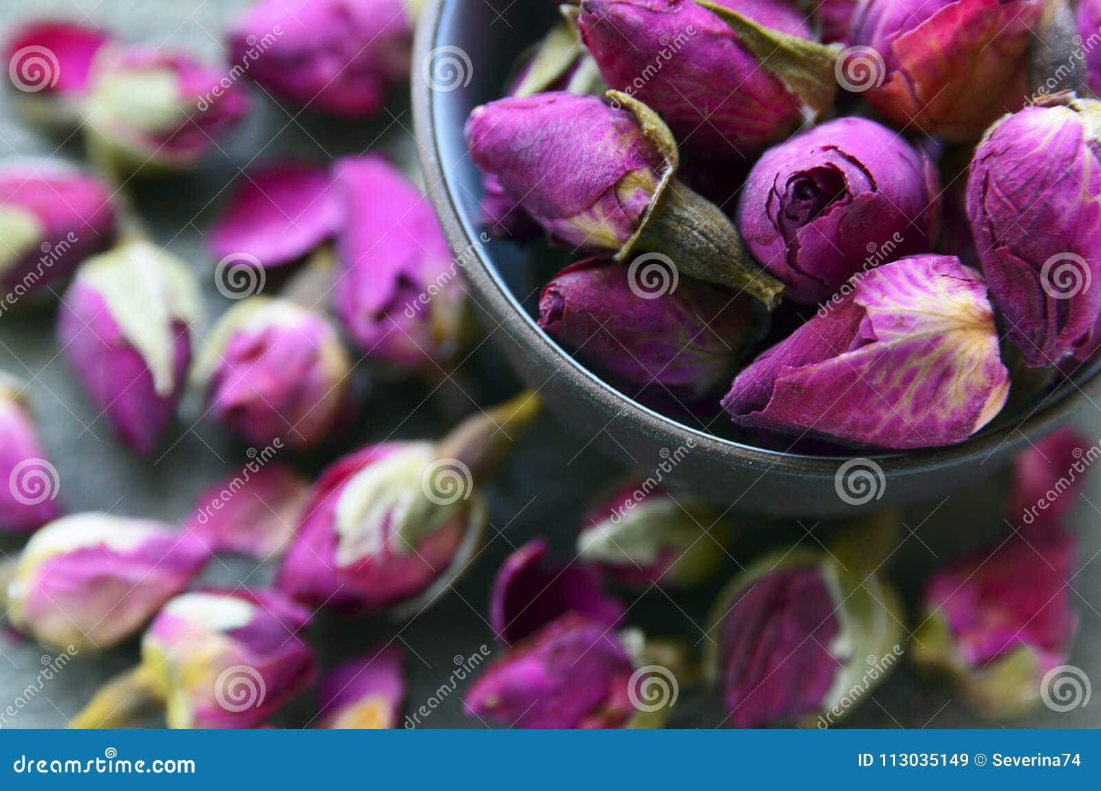 Flores color de rosa secas de los brotes en un cierre del cuenco para arriba Ingrediente asiático para la infusión de hierbas del