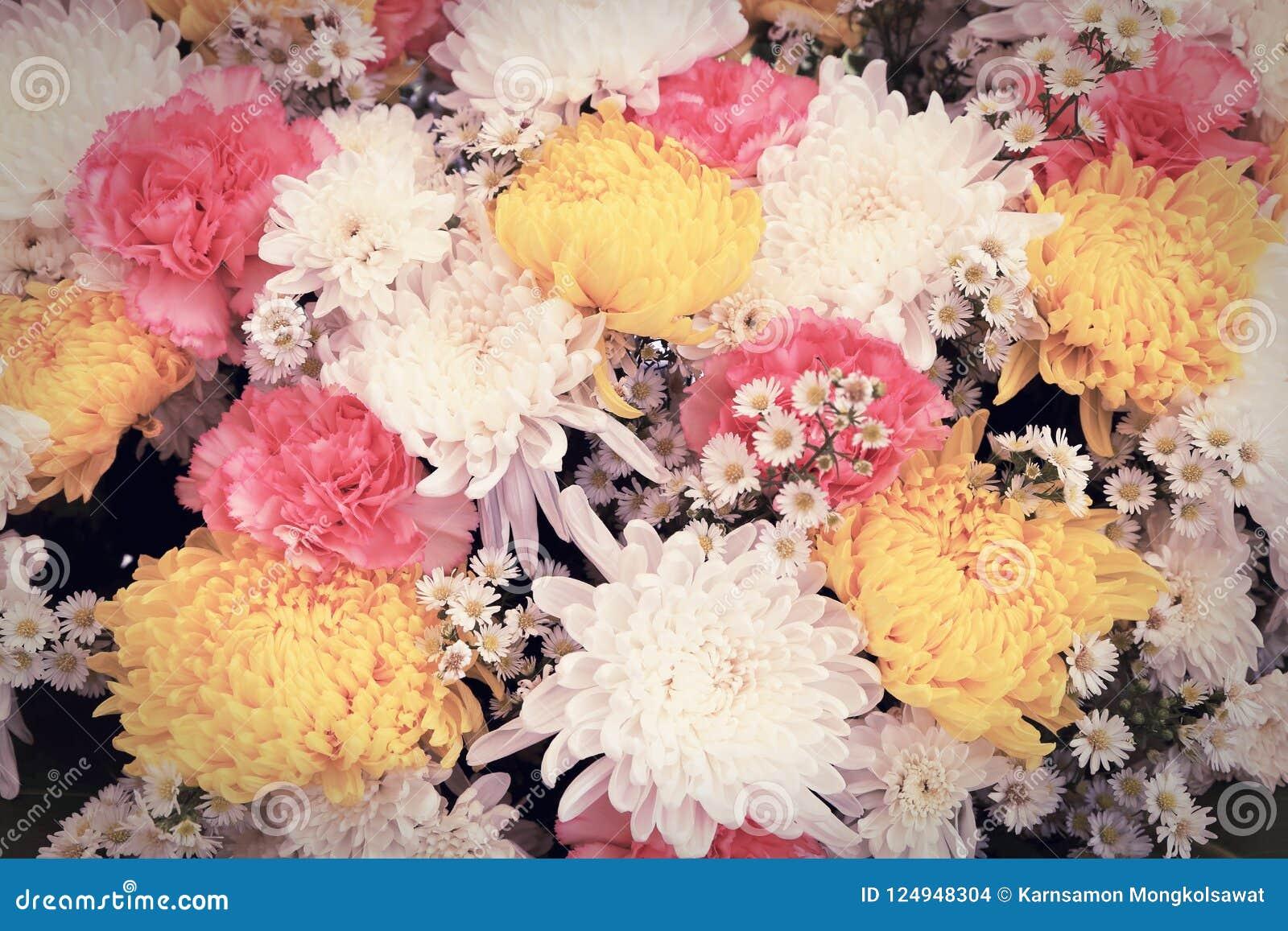 Flores coloridas dispuestas como imagen de fondo natural con los flores blancos, amarillos y rosados Ramo floral entonado vintage