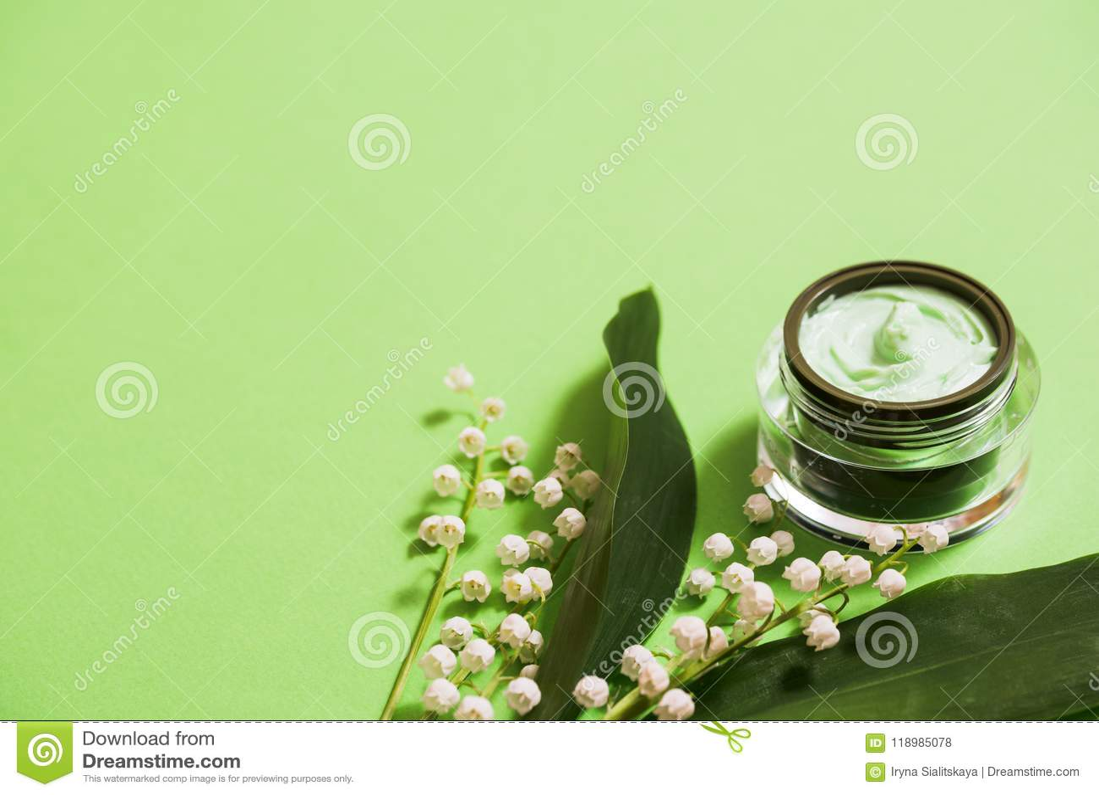 Flores cosméticas de la crema y del lirio de los valles en un fondo verde