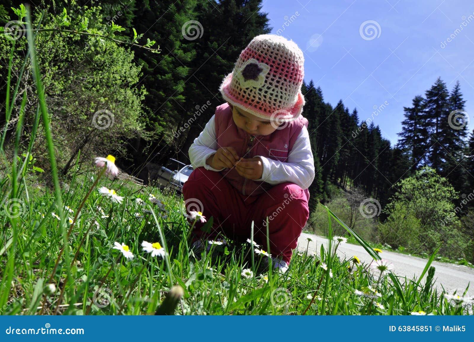 Flores de cheiro da menina pequena bonito da criança