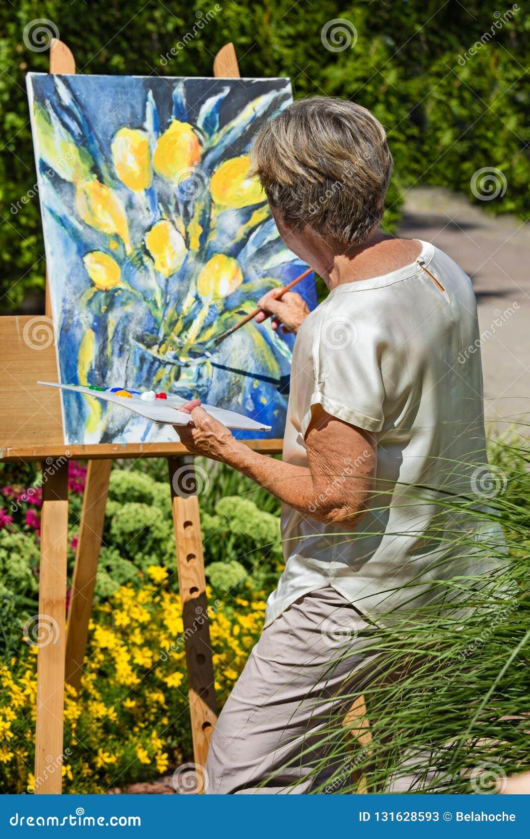 Flores de pintura de la mujer mayor en lona en jardín durante día soleado