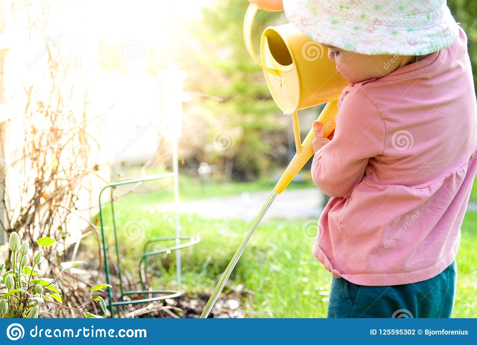 Flores de riego de un pequeño bebé con una jarra amarilla del agua