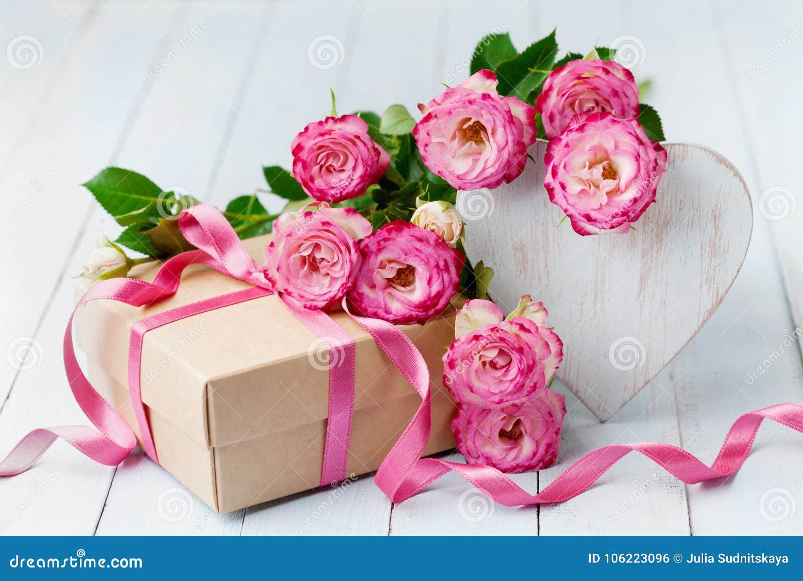 Flores de Rose, corazón de madera y caja de regalo en la tabla rústica azul Tarjeta de felicitación hermosa para el día del cumpl
