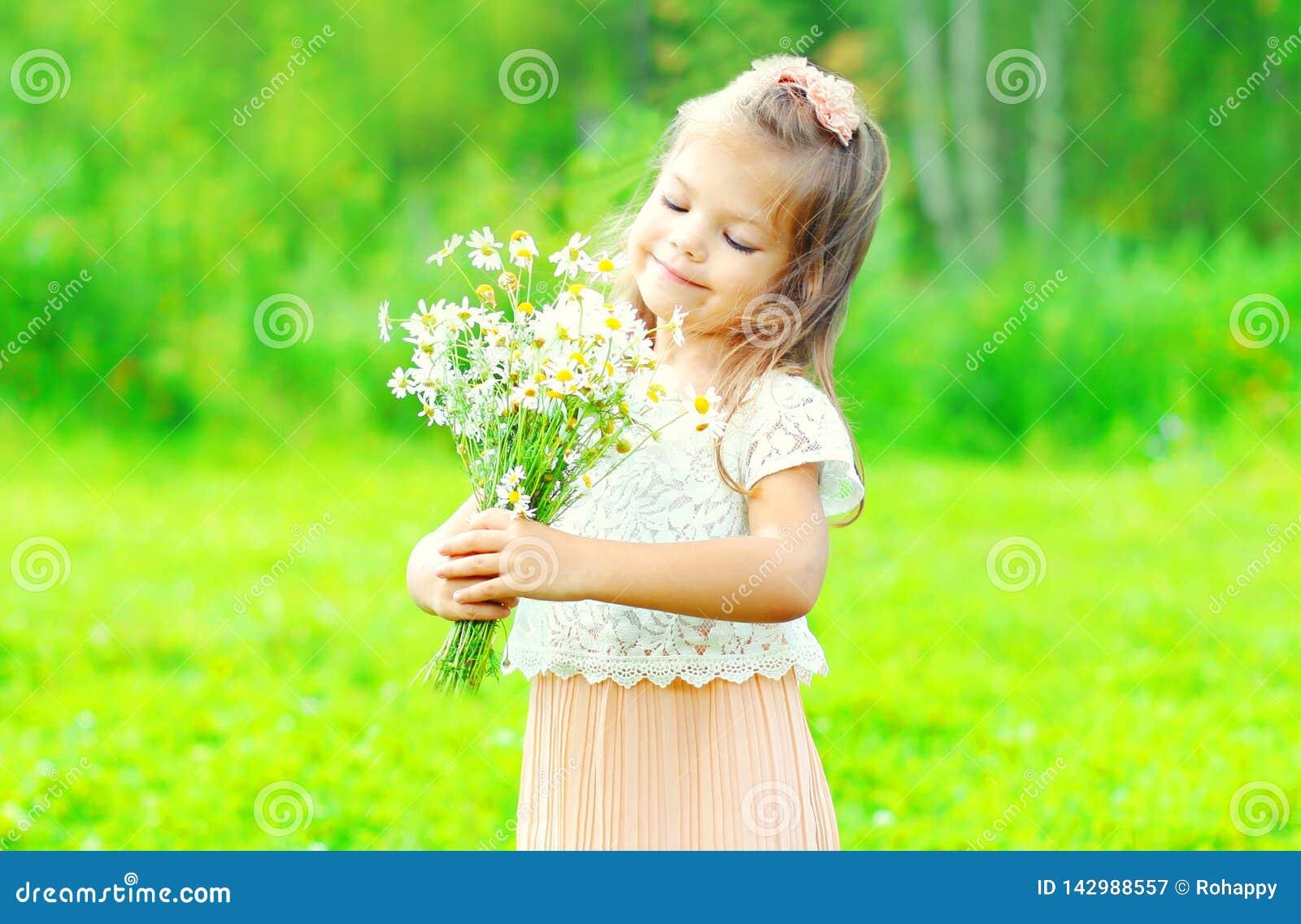 Flores de sorriso felizes do ramalhete da terra arrendada da criança da menina do retrato em suas mãos na mola