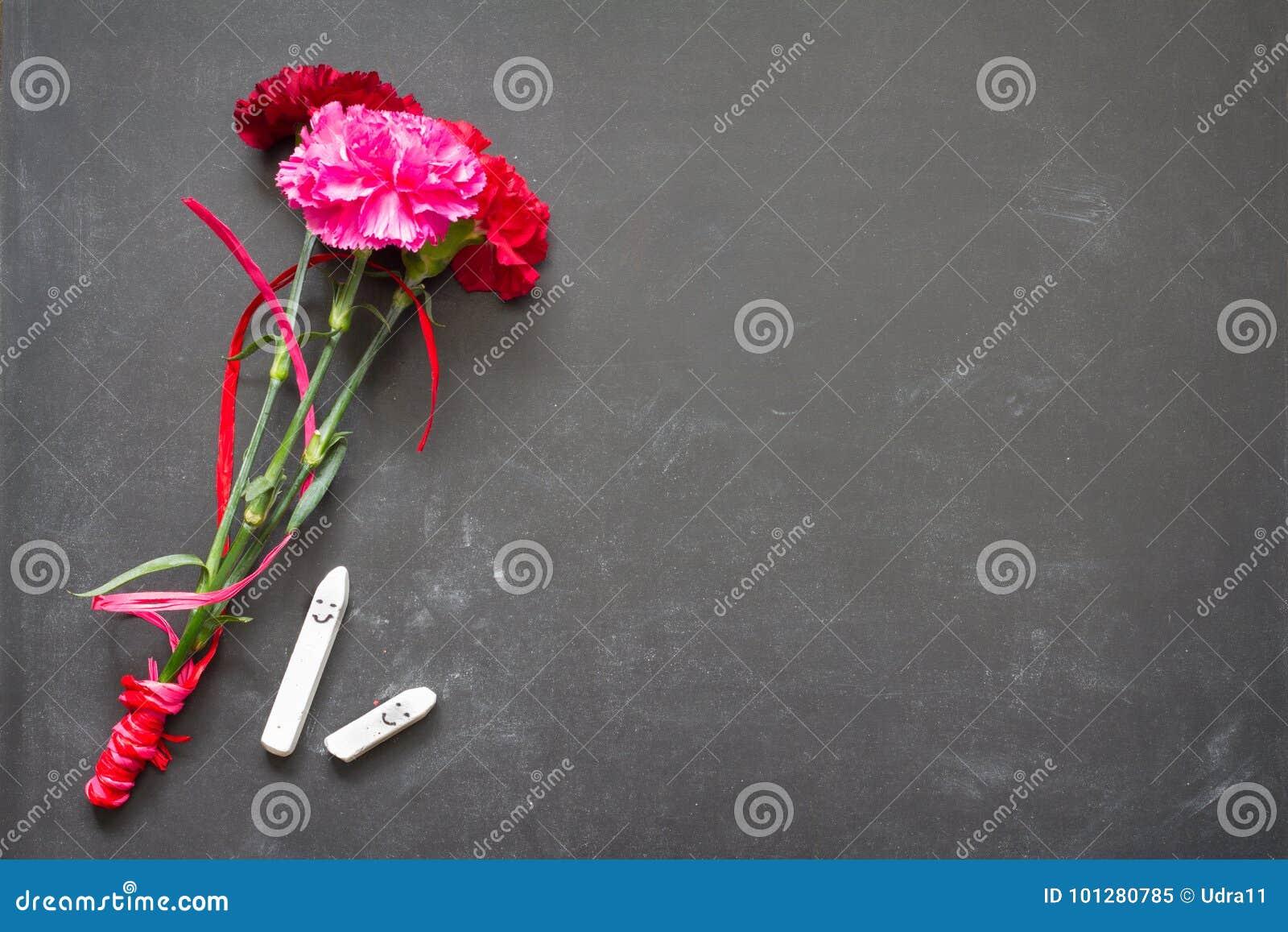 Flores e quadro-negro no conceito do fundo do dia do professor da sala de aula
