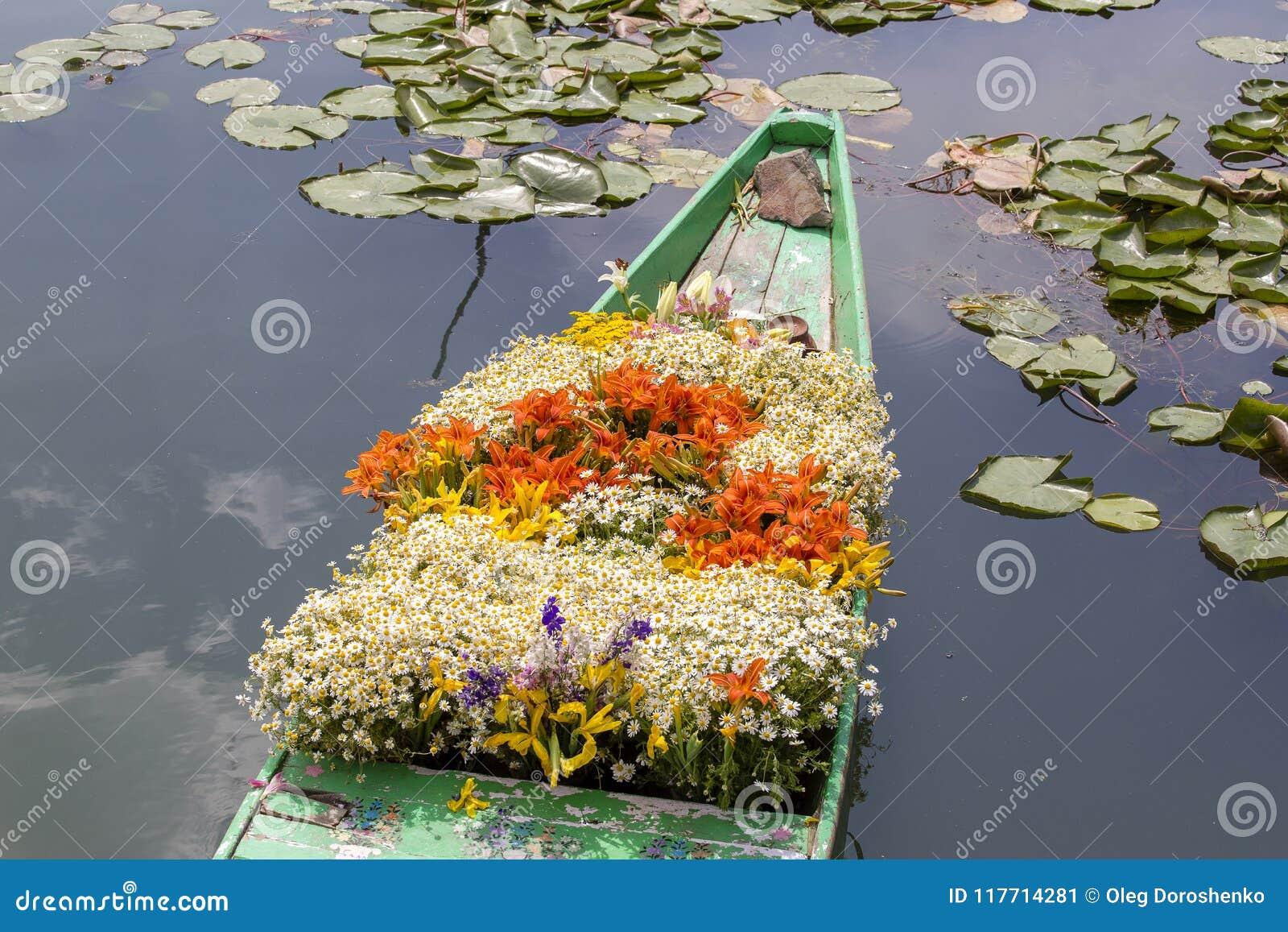 Flores en el barco en el mercado flotante por mañana en Dal Lake en Srinagar, la India
