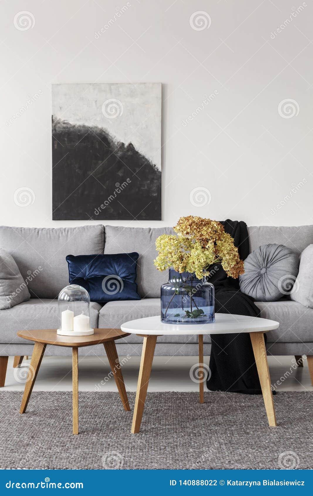 Flores en florero de cristal azul y dos velas blancas en las mesas de centro de madera en sala de estar elegante gris con el sofá