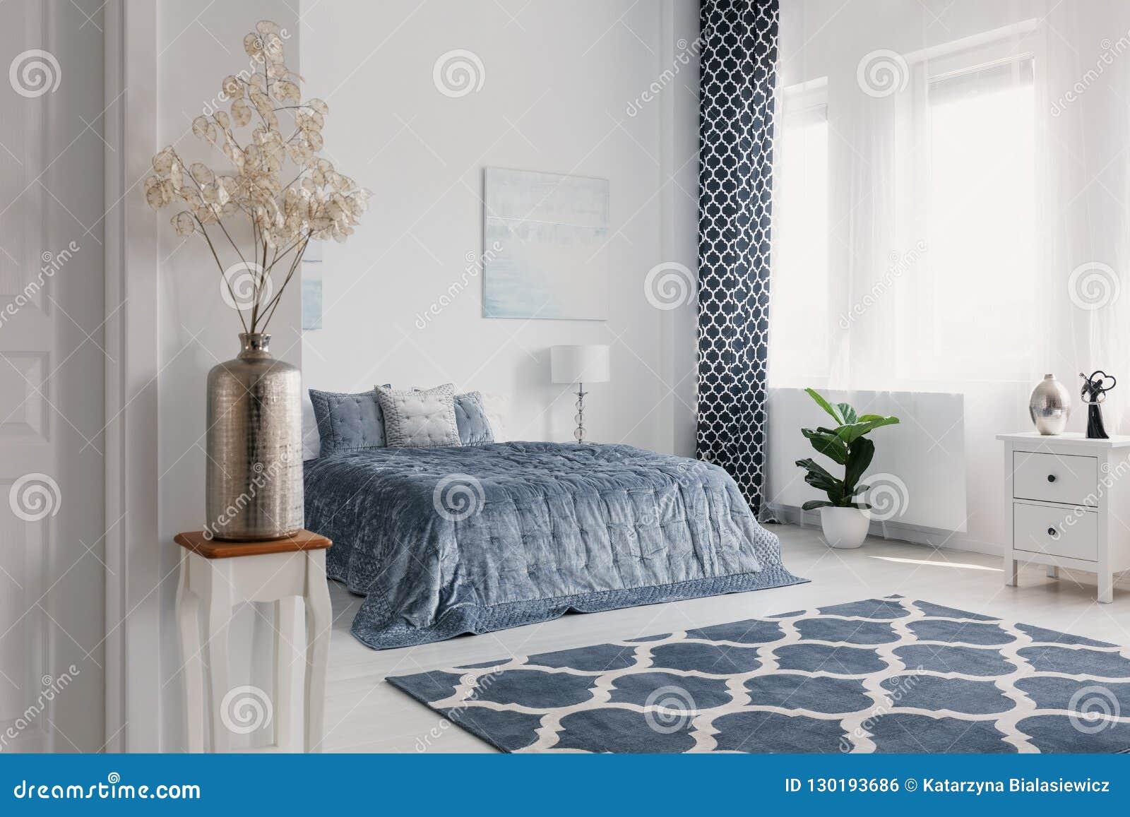Flores en florero del oro en el dormitorio blanco interior con la alfombra modelada delante de la cama azul Foto verdadera