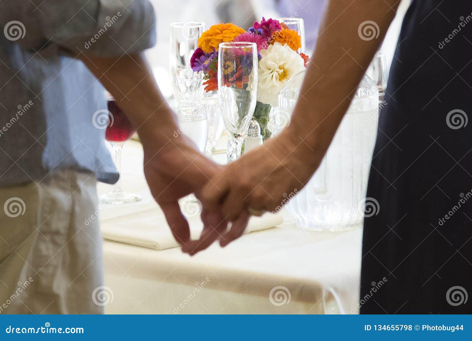 Flores en la tabla de la recepción enmarcada por los pares que llevan a cabo las manos