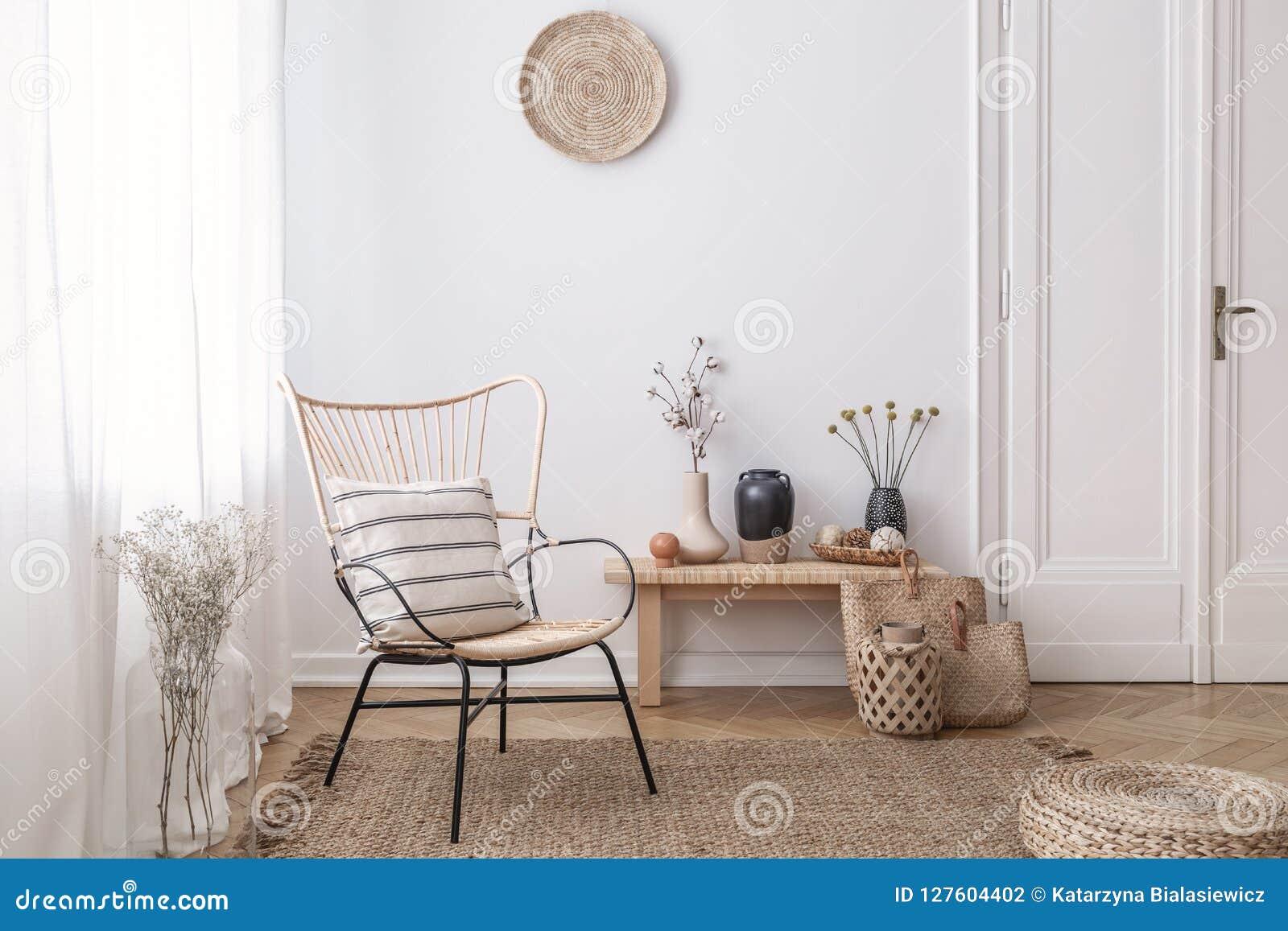 Flores en taburete de madera al lado de la butaca en el interior blanco del desván con el taburete y la placa Foto verdadera