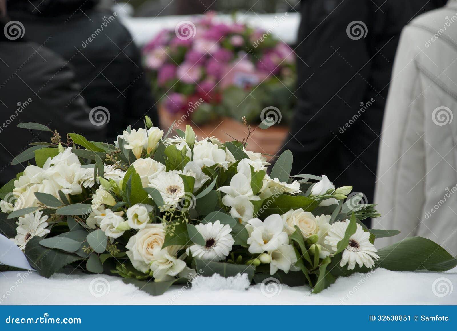 Flores fúnebres blancas en la nieve antes de un caket