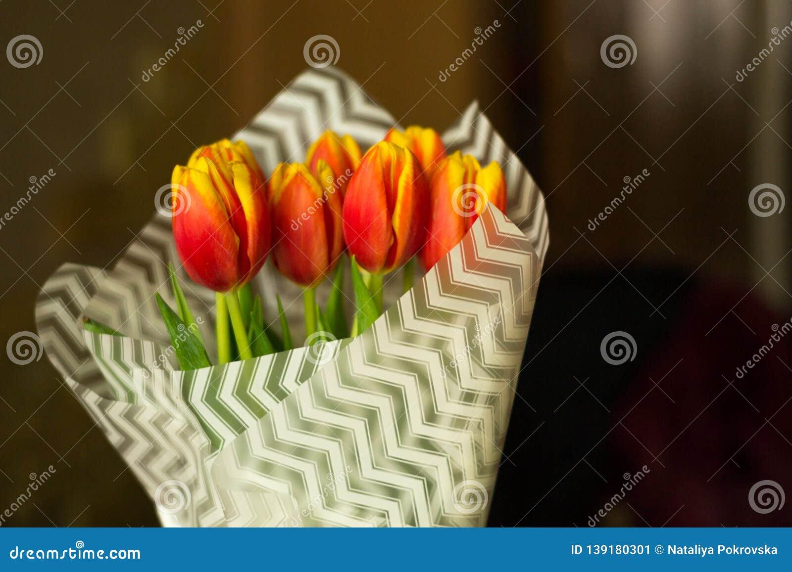Flores frescas del tulipán cubiertas con el Libro Blanco en florero en fondo borroso Días de fiesta de Celebraiting en casa Amor