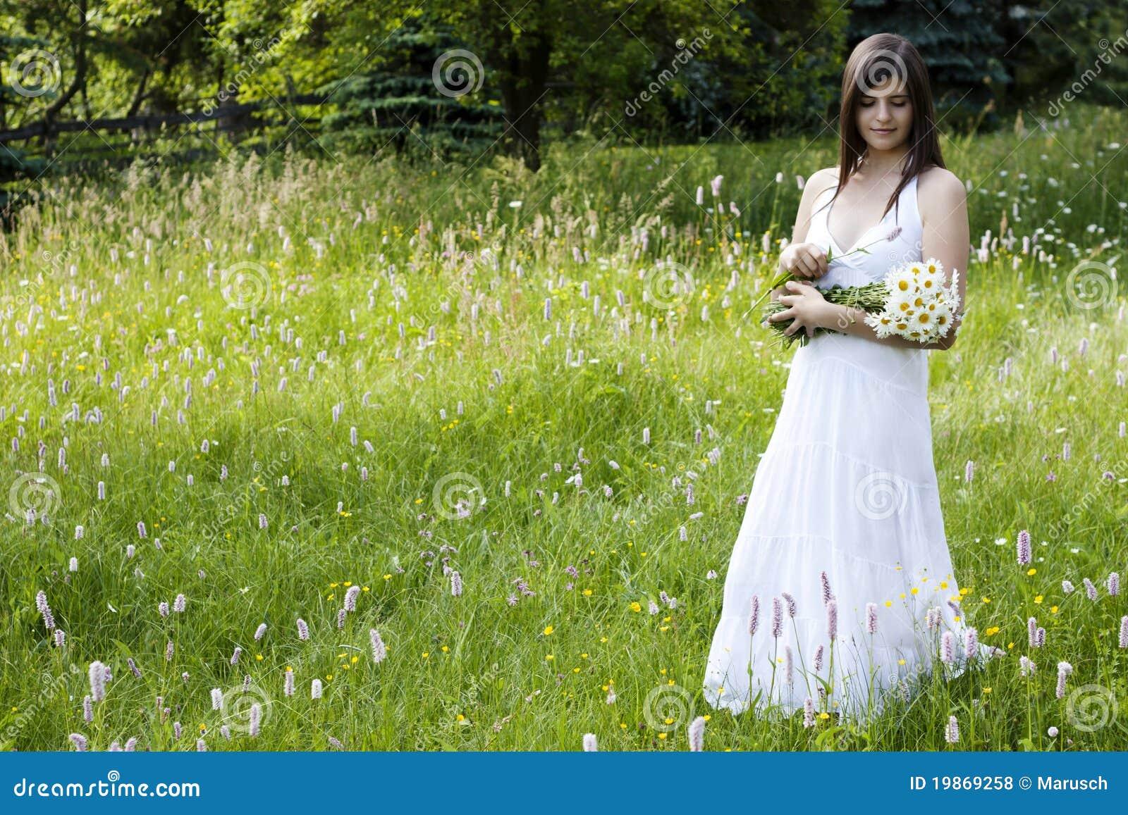 Flores hermosas de la cosecha de la muchacha en un prado