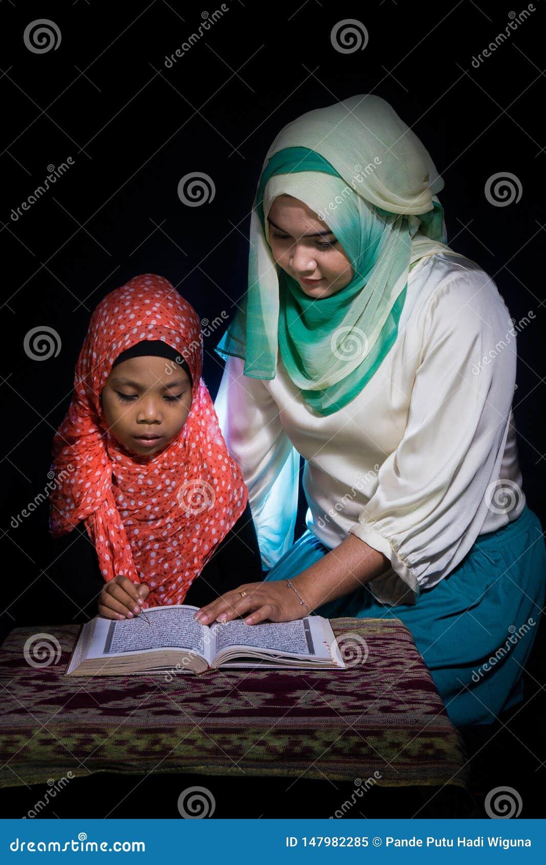 FLORES, 25 INDONESIË-JUNI 2014: Een hijabzuster onderwijst haar zuster die ook een hijab draagt om quran op een lijst met te leze