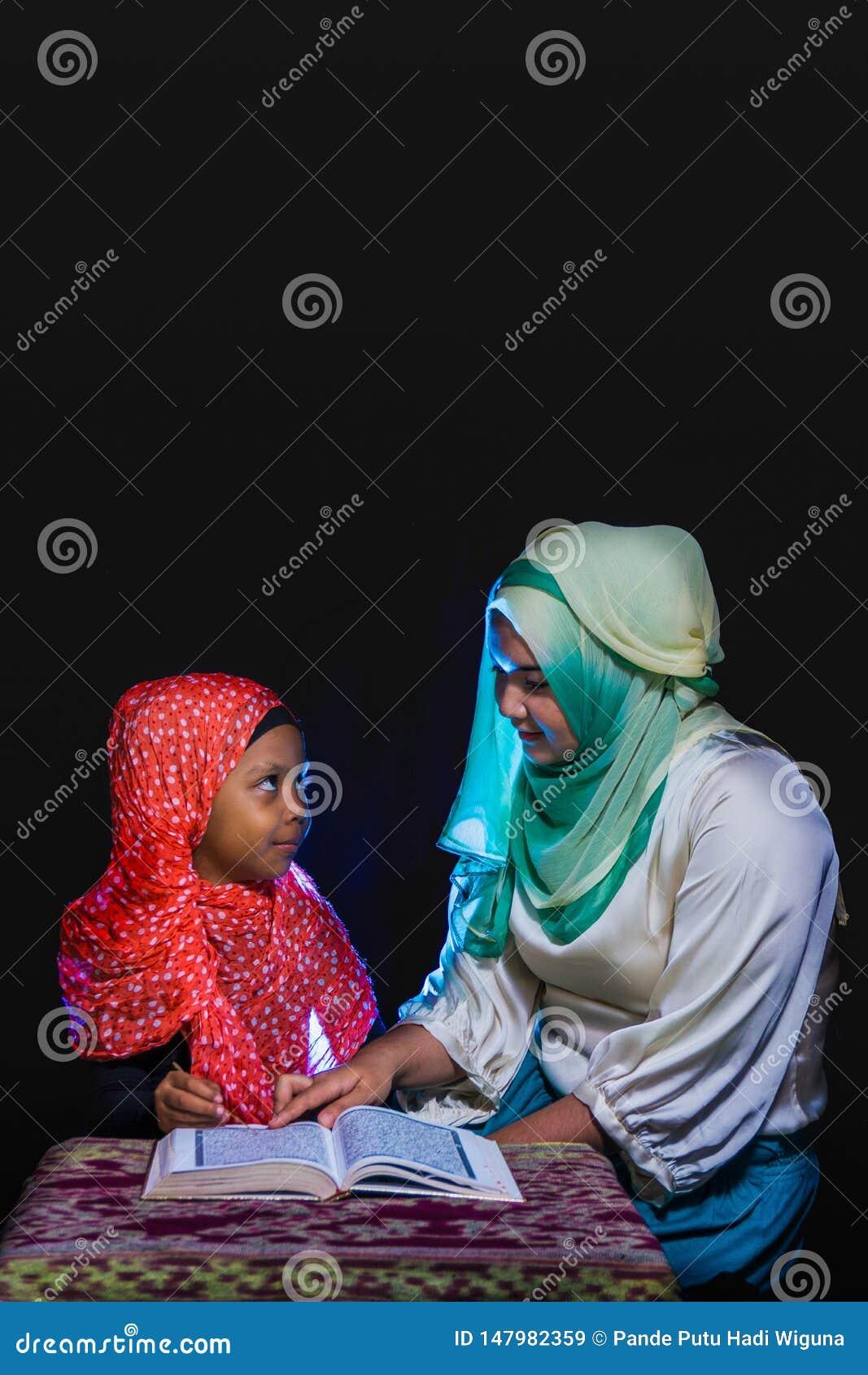 FLORES INDONESIA-JUNE 25 2014: En hijabsyster undervisar hennes syster som b?r ocks? en hijab f?r att l?sa quranen p? en tabell m