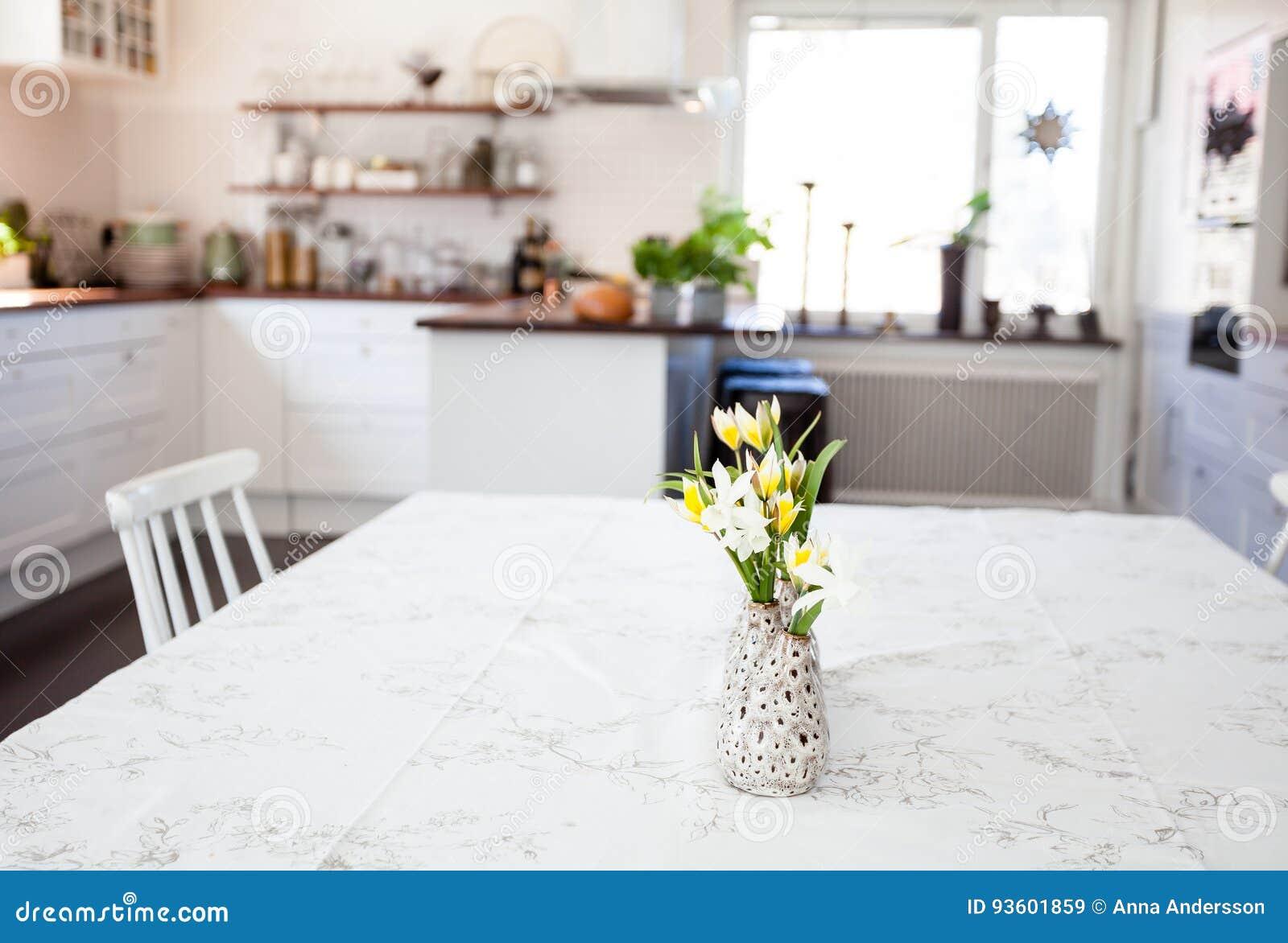 Flores na tabela na cozinha do primeiro plano borrada no fundo