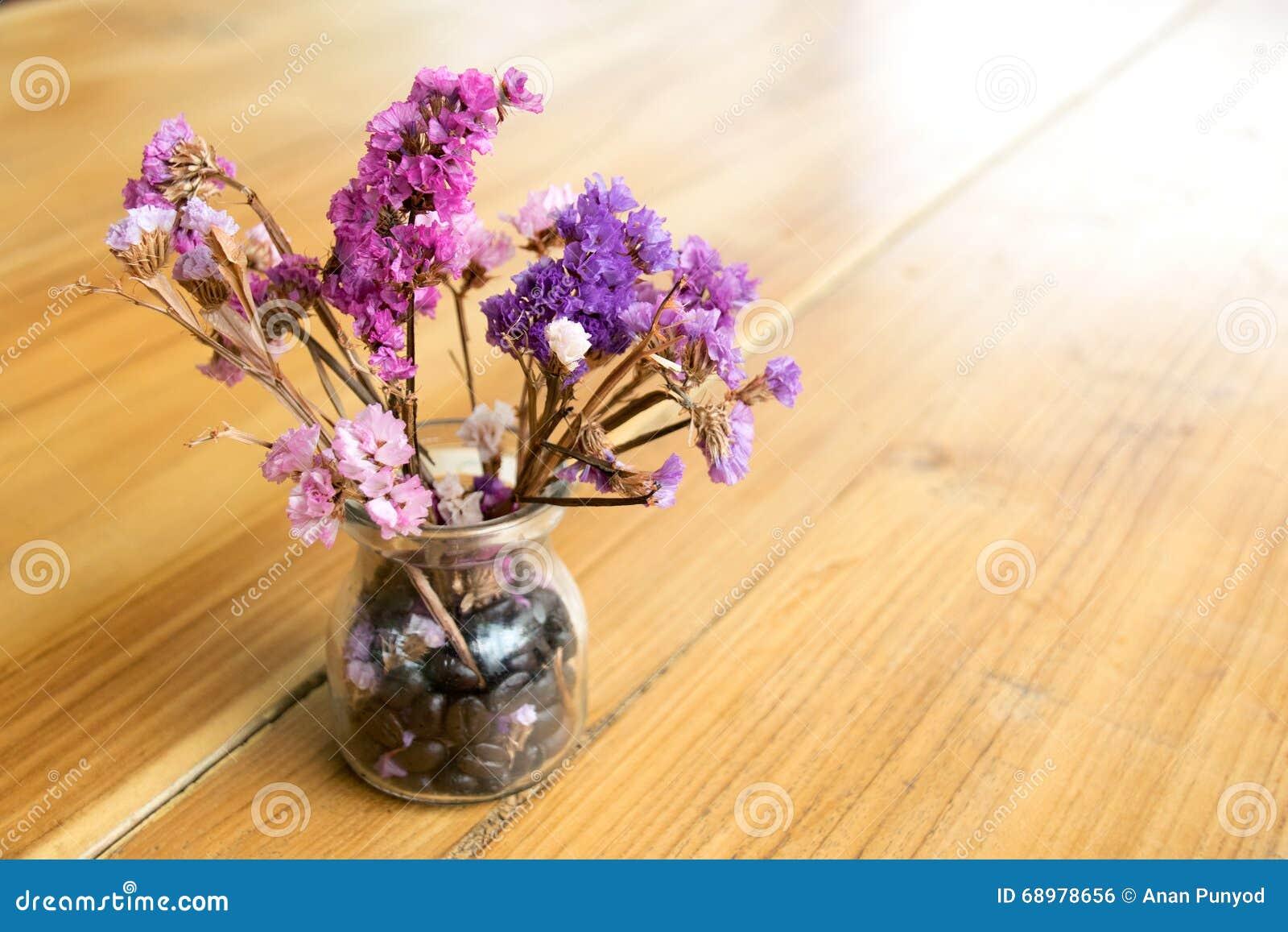Flores púrpuras en un florero de cristal en la tabla de madera