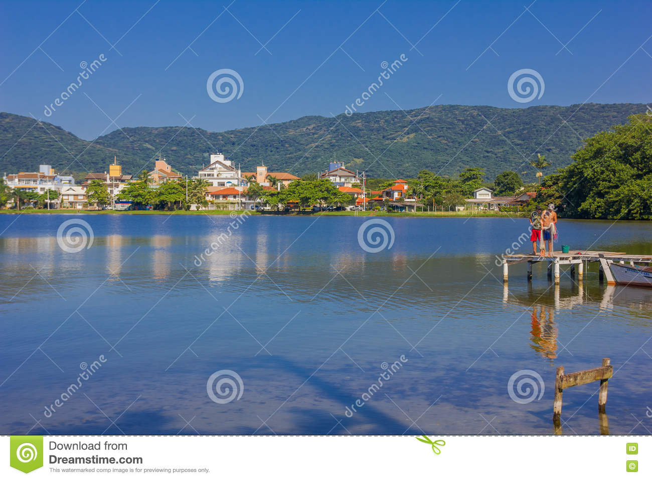 FLORIANOPOLIS, BRAZIL - MAY 08, 2016: two man standing over the dock with a fishing net, reflection of some houses on