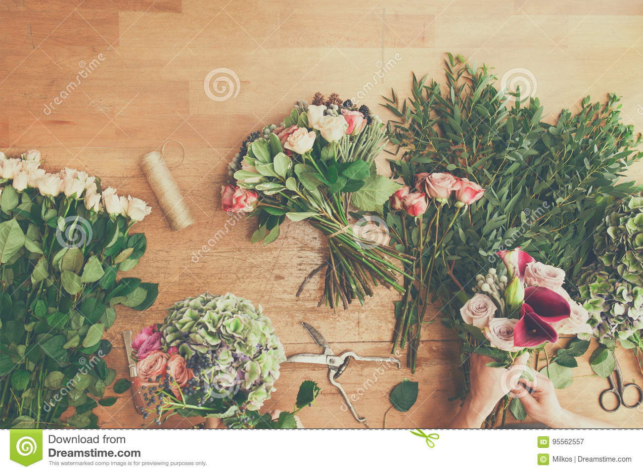 Florist in flower shop delivery make rose bouquet, table top view