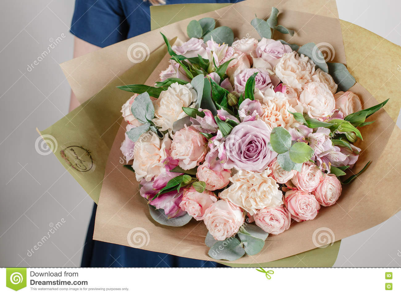 Florist girl with rich bunch flowers. Fresh spring bouquet. Summer Background. Young woman flower for birthday or mother