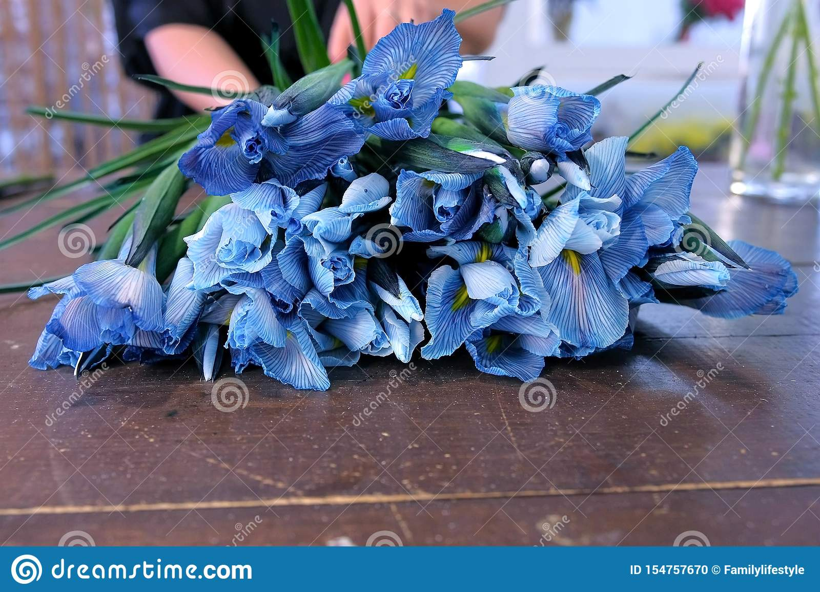 Florist Woman Creates Bouquet From Blue Iris Flowers On Table For Sale In Shop Stock Photo Image Of Hands Business 154757670