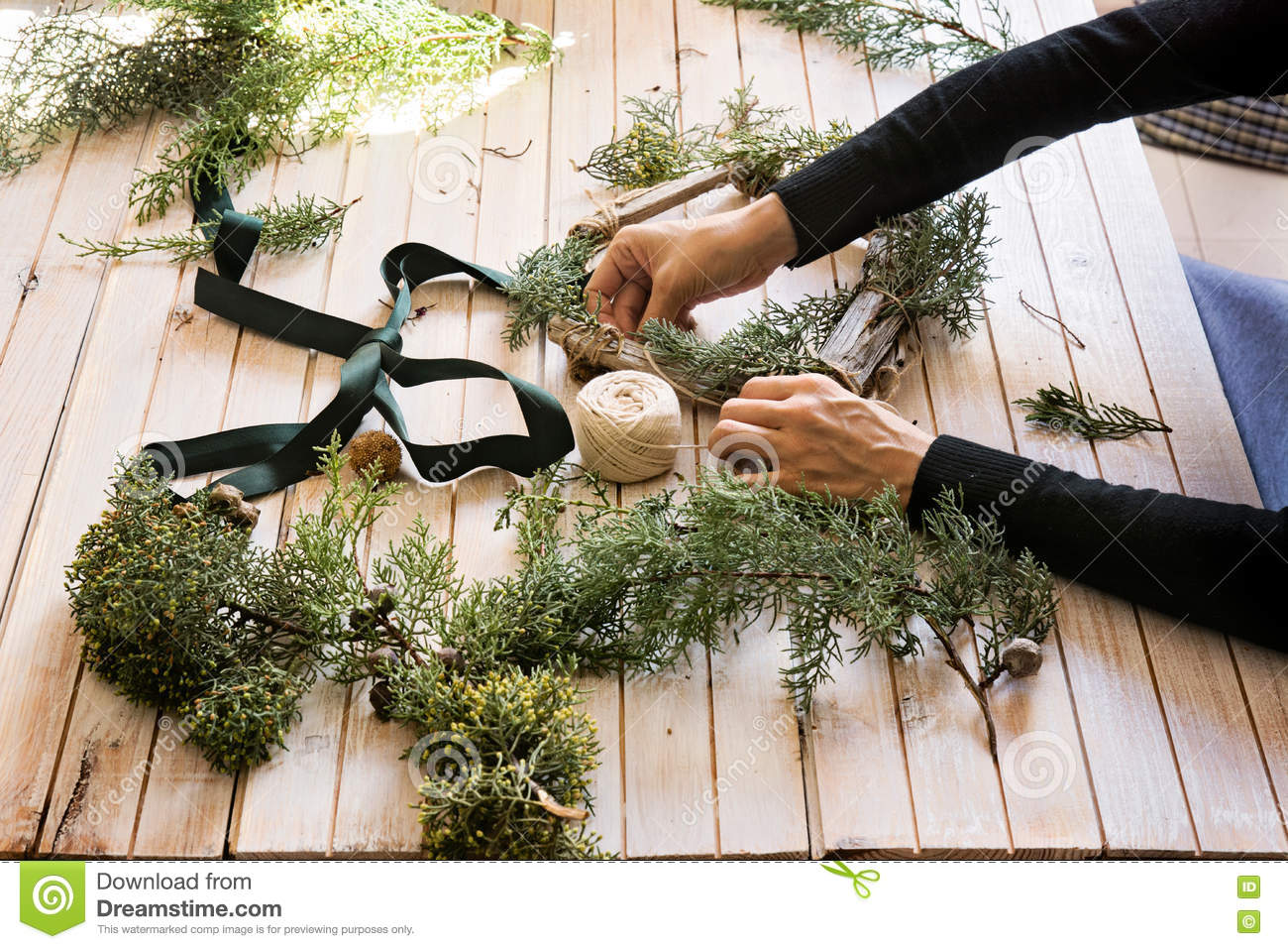 Florist At Work Creating A Wooden Wreath With Christmas Red Ba