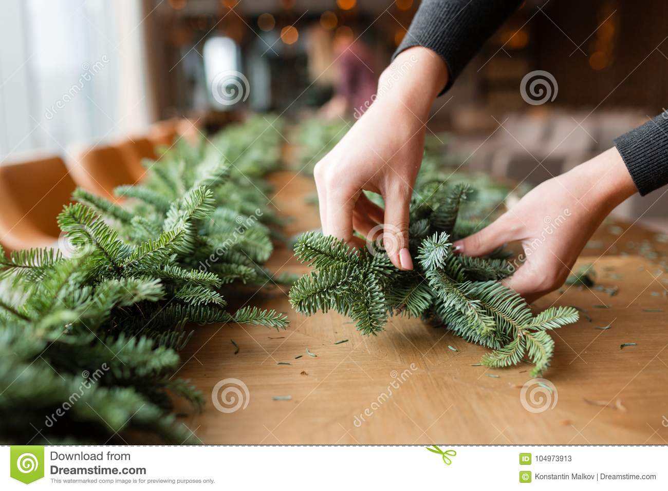 florist at work woman hands making christmas decorations garland of fir happy new year