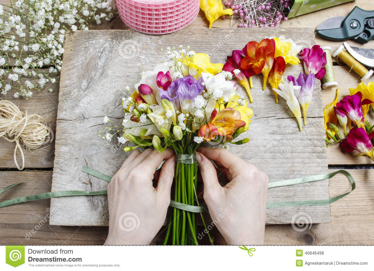 Florist at work woman making bouquet of freesia flowers stock photo woman making bouquet of freesia flowers izmirmasajfo