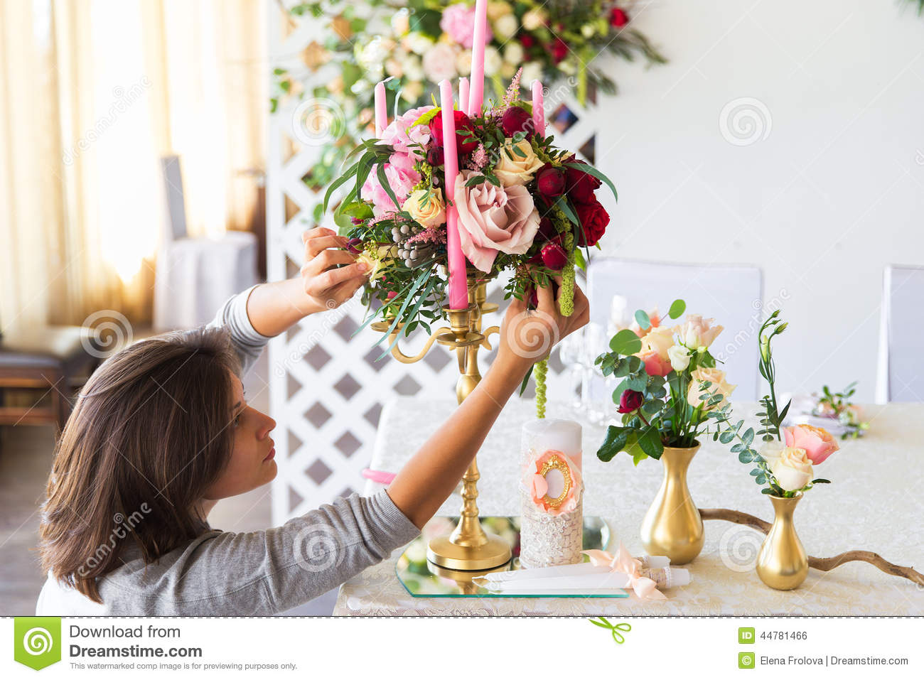 Florist at work. Woman making spring floral decorations the wedding table , the bride and groom. Flowers, candles, a bottle of ch