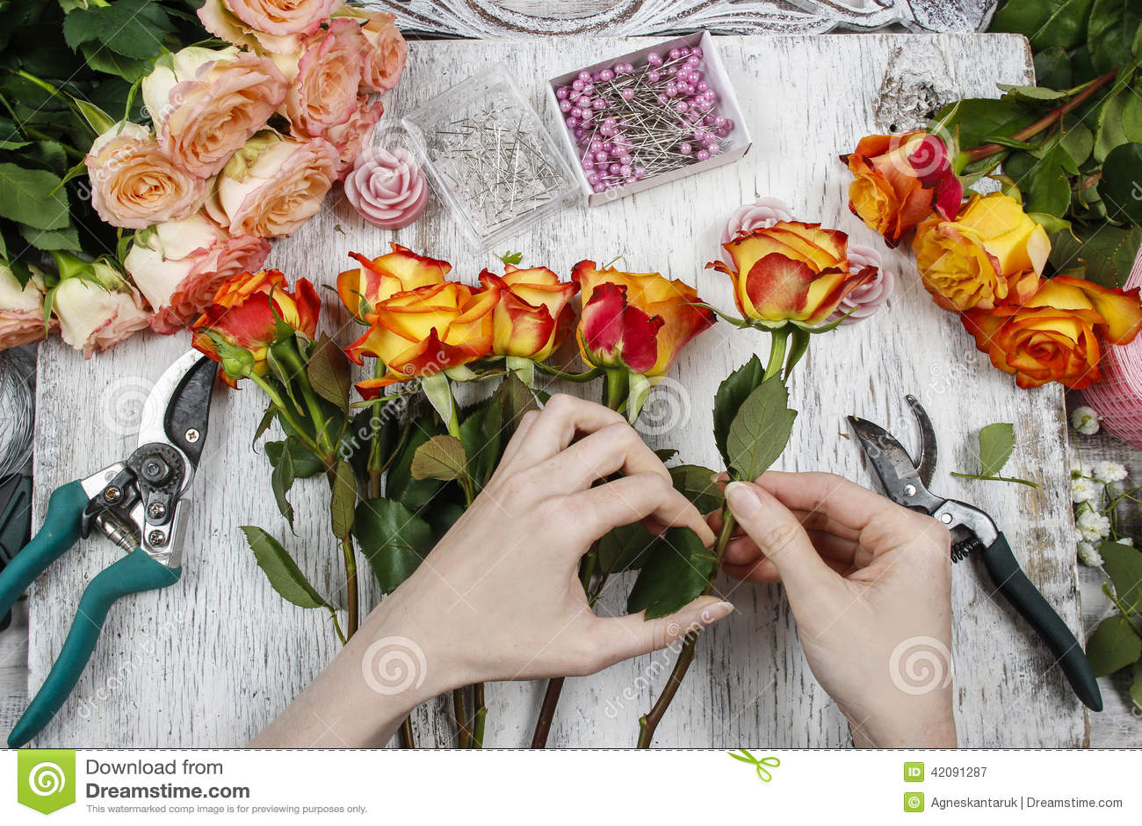 Florist at work. Woman making wedding bouquet of orange roses