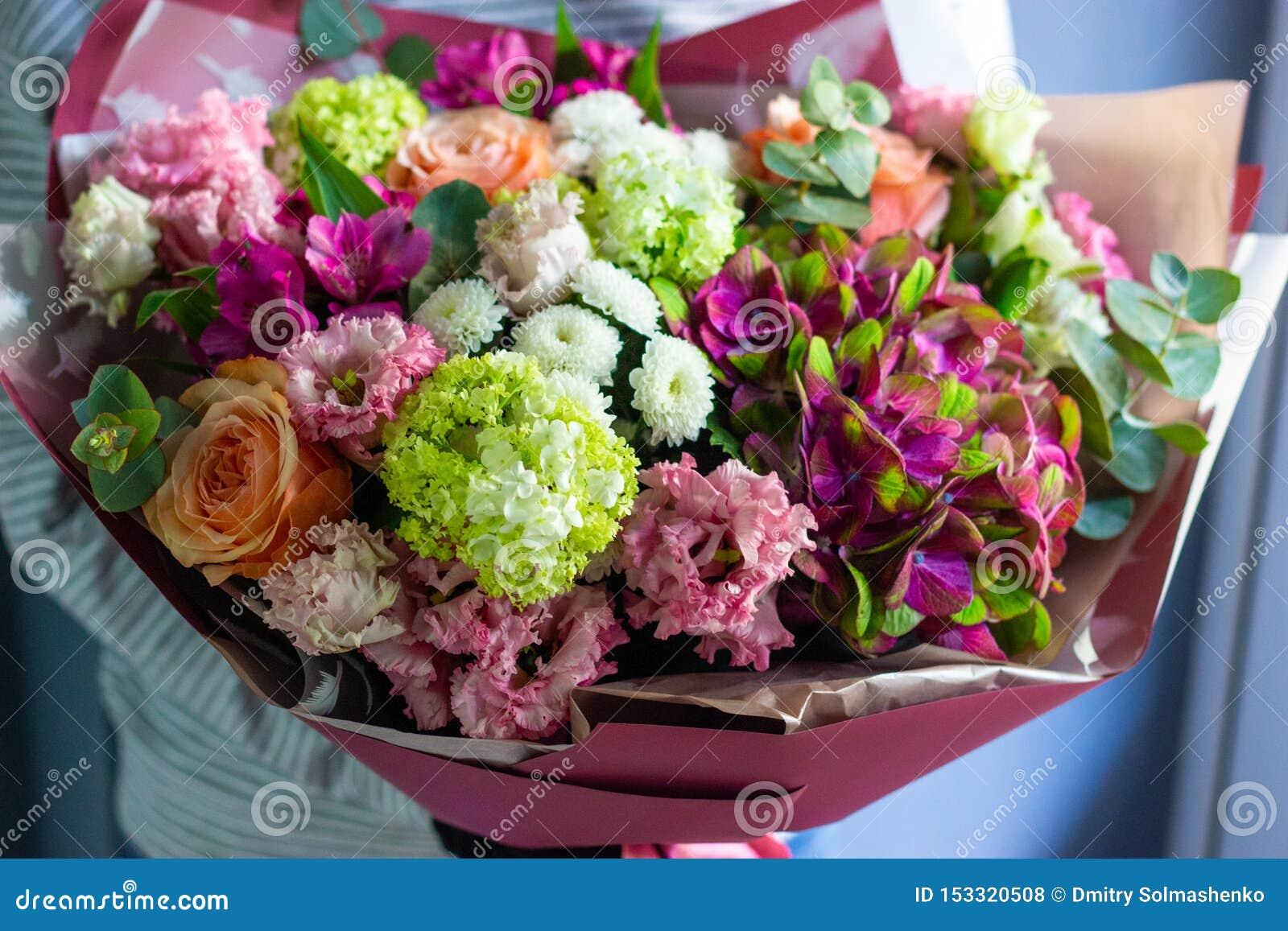 Florista que guarda um ramalhete colorido das flores em seu fundo floral das mãos