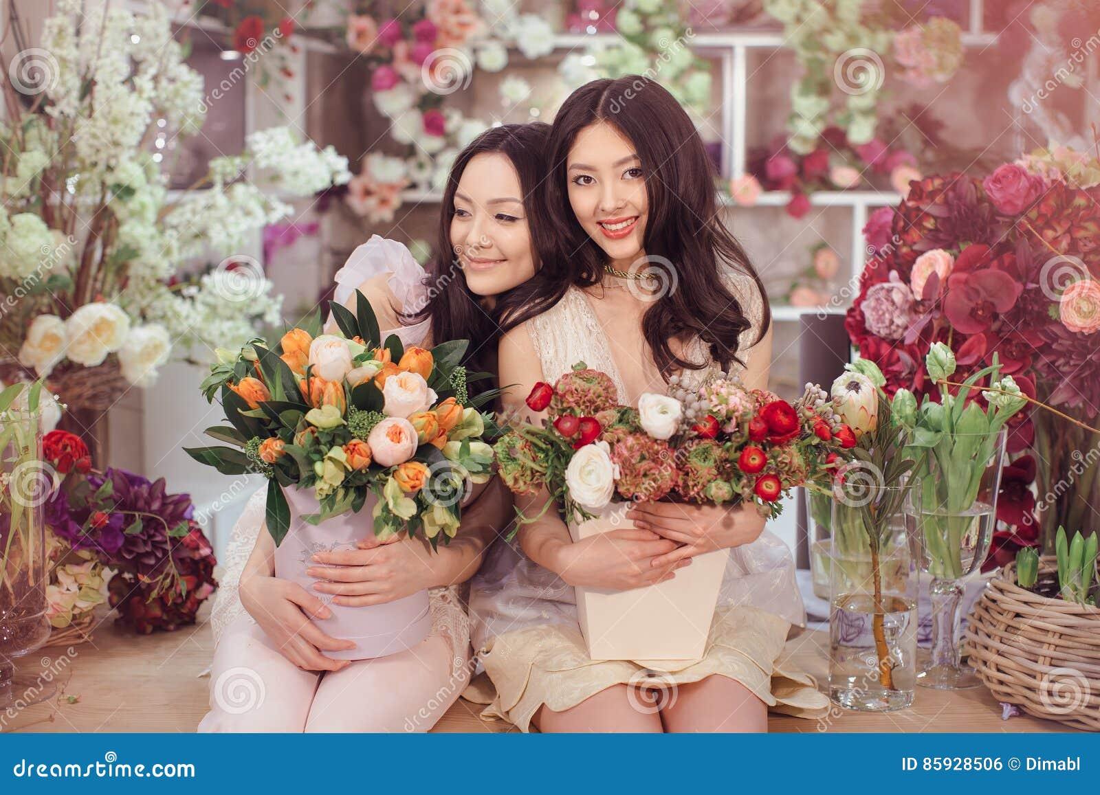 Floristas asiáticos hermosos de las mujeres con el ramo de flores en tienda de flor