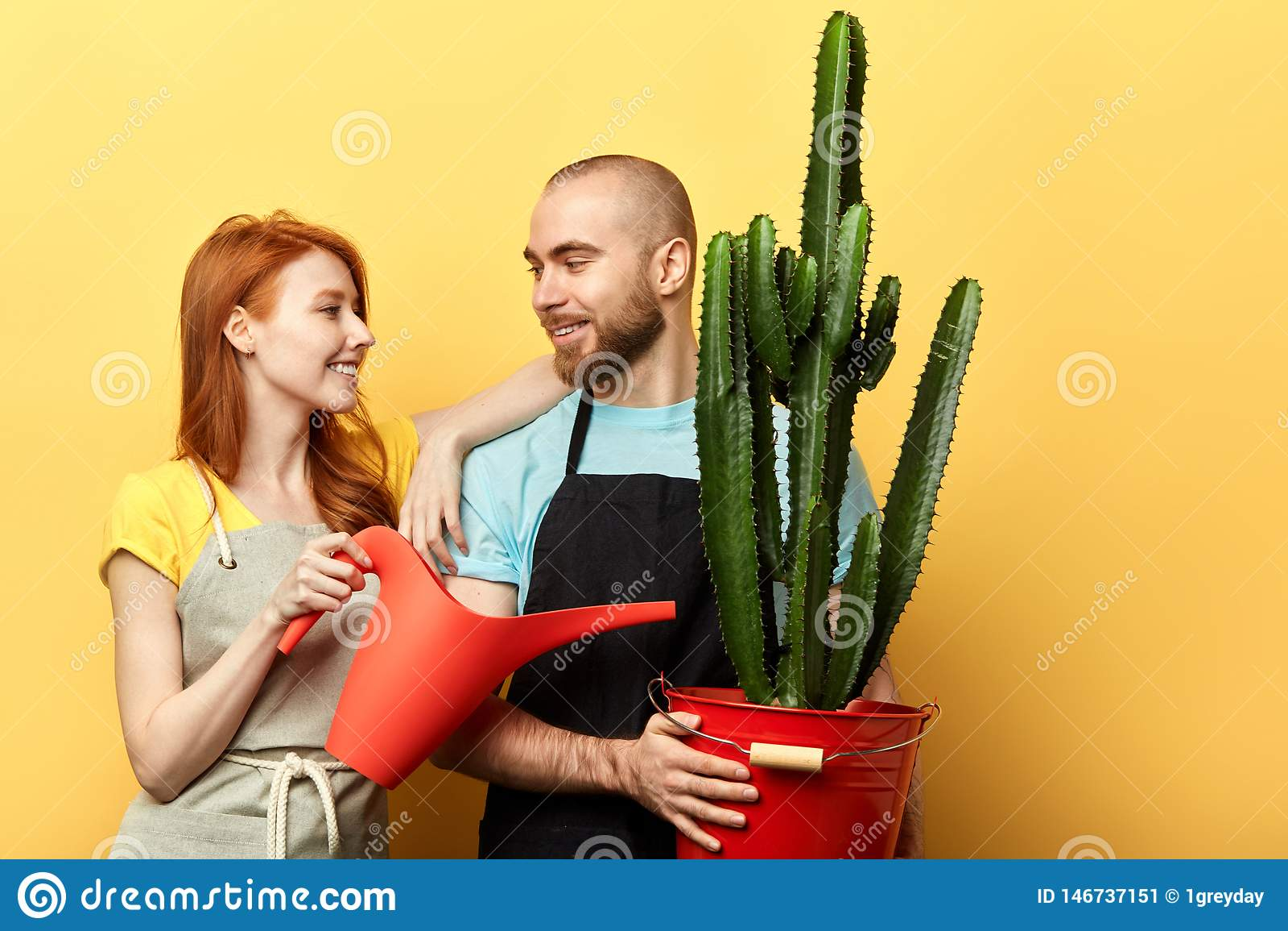 Floristas positivos felices con la regadera que presenta a la cámara