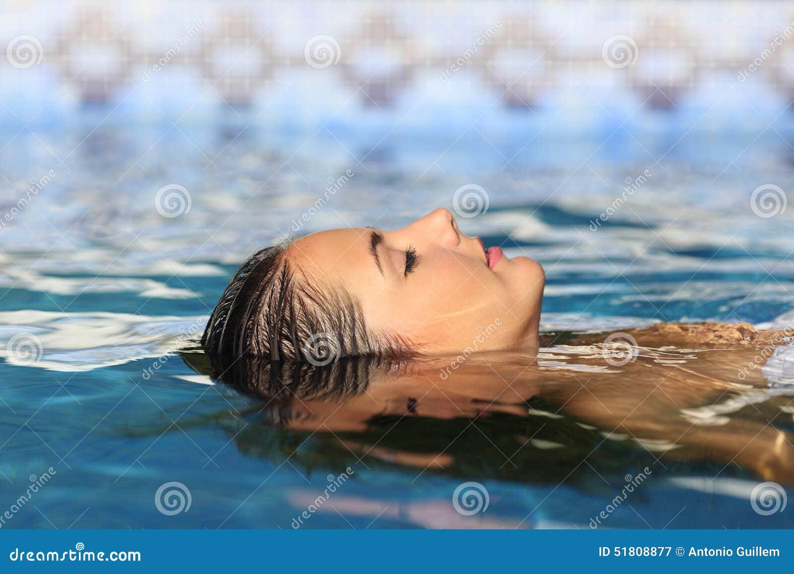 Flotación de relajación de la cara de la mujer en el agua de una piscina o de un balneario